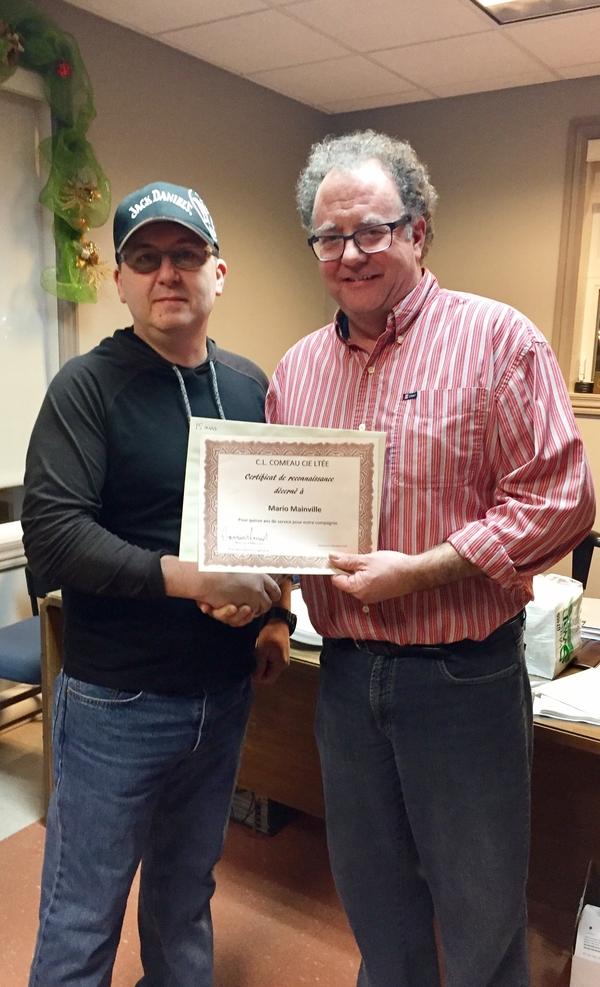 Mario Mainville, contremaître de l'entrepôt, reçoit son certificat pour 15 années de service du directeur général Normand Mourant