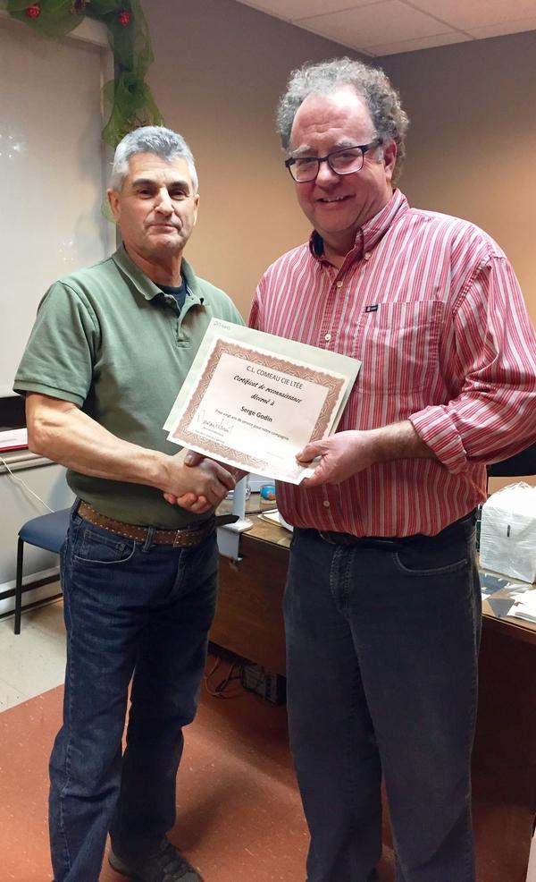 Serge Godin, préposé aux commandes, reçoit son certificat pour 20 années de service du directeur général Normand Mourant